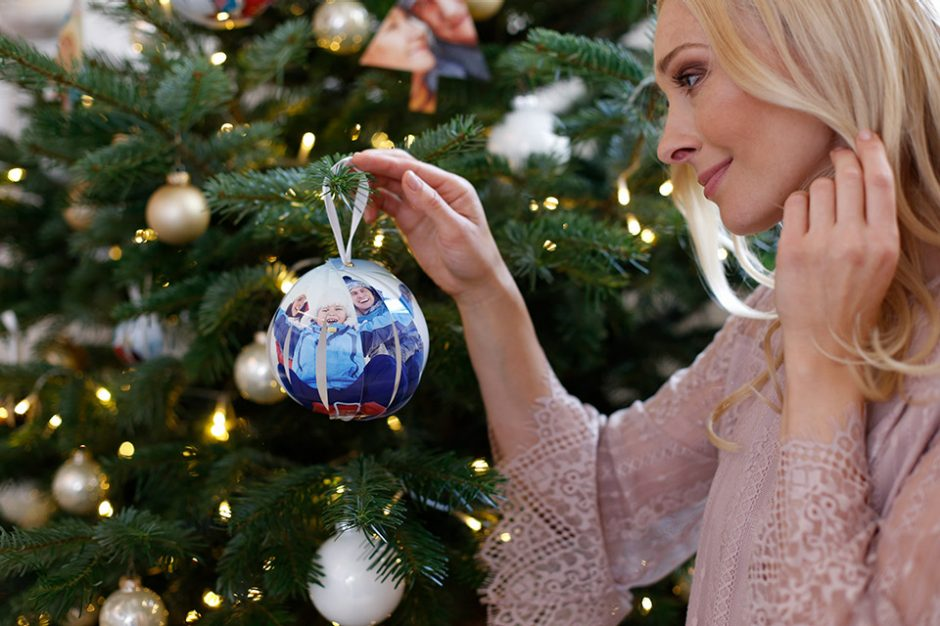 A woman hangs up a self-made photo ball while decorating the Christmas tree