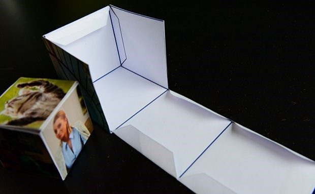 An example of photos being folded and glued following the cube cutout pattern displayed next to the end result