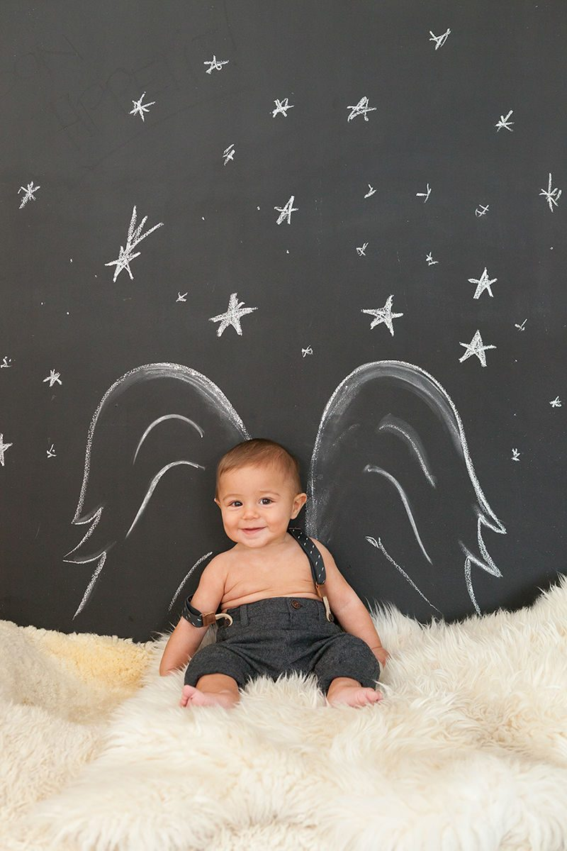 A baby positioned in front of a wall decorated with angel wings and stars