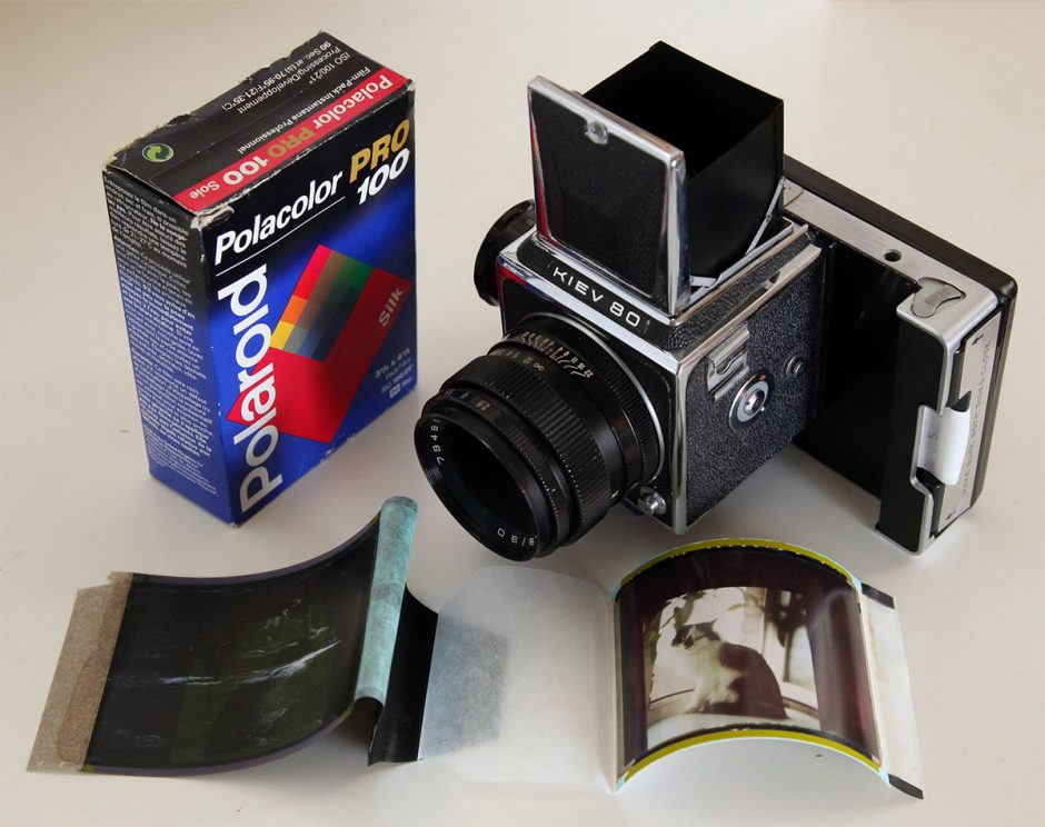 Polacolor film sitting next to an instant camera