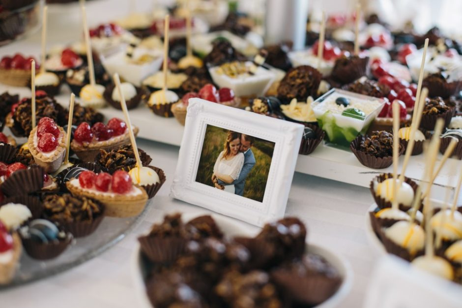 A beautiful picture frame sitting on a cake buffet displaying a digital photo of the bridal couple
