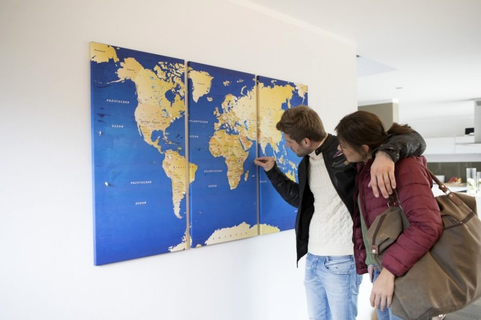 A couple marking a new travel destination on their world map