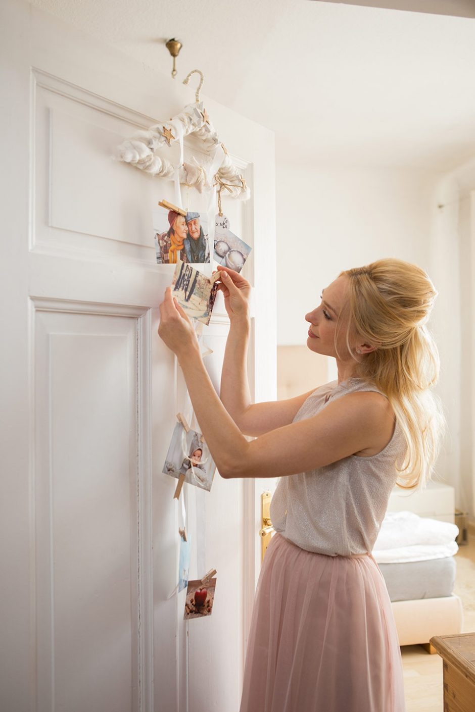 A woman standing in front of a door adorning her garland with photos