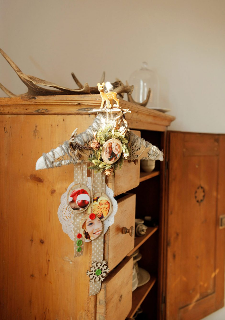 A clothes hanger, bedecked with Christmas decorations and photos, hanging on a cabinet